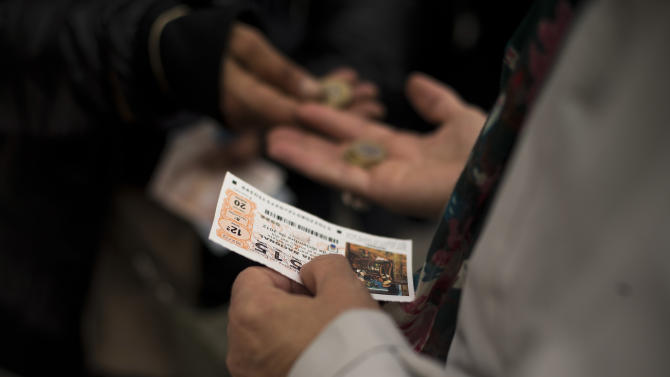 """A man buy tickets for the cash-strapped country's famed Christmas lottery, in Madrid, Friday, Dec. 21, 2012. Many players say they're hoping to win so they can pay off debt or help relatives facing heavy economic burdens. Known as """"El Gordo"""" (The Fat One) and billed as the world's richest lottery, the drawing will hand out about 2.5 billion of euro ($3.3 billion) on Saturday. The top prize is about 400,000 euro ($530,000) but there are expected to be hundreds or thousands of tickets awarded for that amount. (AP Photo/Daniel Ochoa de Olza)"""