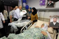 Palestinian mother Dala looks over at her new born son as she lays under a photograph of her imprisoned husband Amer al-Zein at the al-Arabi hospital in the northern Palestinian West Bank city of Nablus. Baby Muhanad was born after his father, who is serving life in an Israeli prison, was able to have his sperm transferred to Nablus