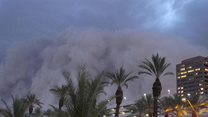 "A dust storm known as a ""habub"" rolls into downtown Phoenix on Tuesday night, July 5, 2011, bringing strong winds and low visibility. Habubs are part of Arizona's annual monsoon season, which is now in full swing. (AP Photo/Amanda Lee Myers)"