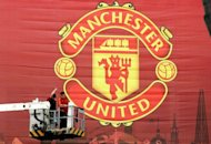 Workmen adjust a large Manchester United banner at Moscow&#39;s Luzhniki stadium in 2008. Legendary British football club Manchester United, overloaded with debt since their takeover by a billionaire American family of investors, is moving to raise cash through a US share sale