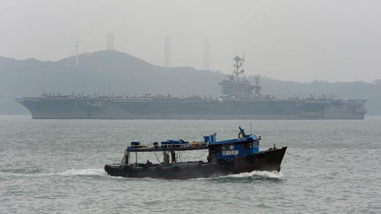 A fishing boat (foreground) passes by the aircraft carrier USS George Washington as it sails out of Hong Kong on November 12, 2013 to join the rescue and relief operations in the Philippines following Super Typhoon Haiyan