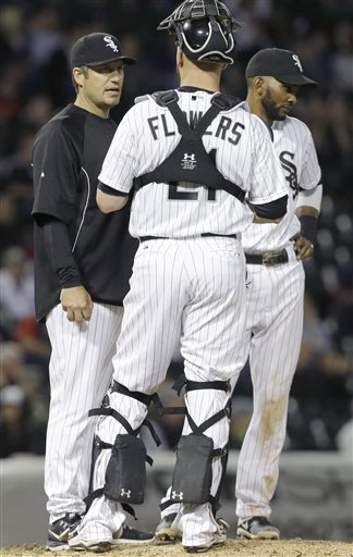 Chicago White Sox manager Robin Ventura, left, talks with catcher Tyler Flowers, center, as shortstop Alexei Ramirez, right, looks down during the eighth inning of a baseball game against the Boston R