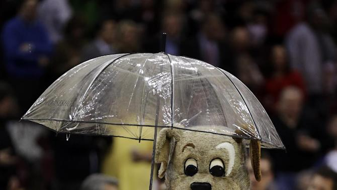 "Cleveland Cavaliers mascot ""Moondog"" holds an umbrella over his head before an NBA basketball game between the Cleveland Cavaliers and the Miami Heat Wednesday, March 20, 2013, in Cleveland. The game was delayed due to a fluid leaking from the scoreboard. (AP Photo/Tony Dejak)"