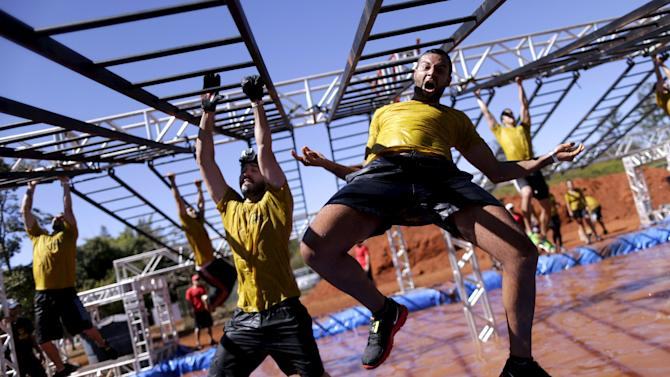 A man jumps as he attempts an obstacle during the Bravus Race competition in Brasilia