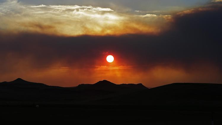 The sun sets through wildfire smoke Sunday, June 23, 2013, near Monte Vista, Colo. A large wildfire near a popular summer retreat in southern Colorado continues to be driven by winds and fueled by dead trees in a drought-stricken area, authorities said. (AP Photo/Gregory Bull)