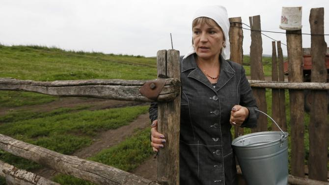 File photo of Zoya Lipnyagova carrying a bucket at her house farm in the village of Kluchi