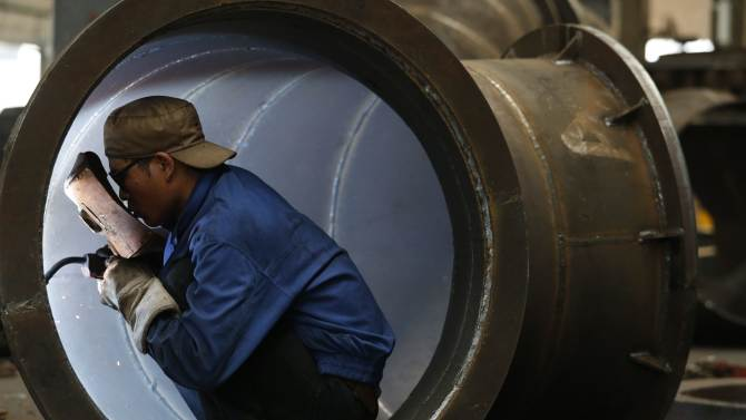 An employee welds a water turbine at a factory in Jinhua, Zhejiang province