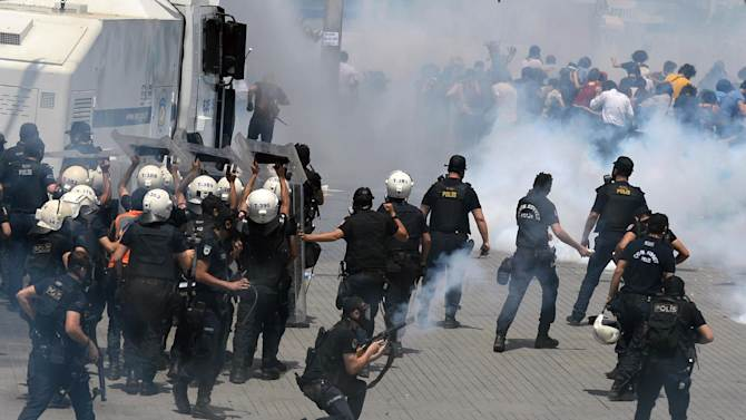 Riot police clash with demonstrators after they used tear gas and pressurized water in a dawn raid on Friday to rout a peaceful demonstration by hundreds of people staging a sit-in to prevent the uprooting of trees at an Istanbul park, Turkey, Friday, May 31, 2013. Several protesters were injured when a wall they climbed collapsed during a police chase, and Ahmet Sik, a prominent journalist was hospitalized after being hit in the head by a tear gas canister. Police moved in to disperse the crowd on the fourth day of the protest against a government plan to revamp Istanbul's main square, Taksim. Officers then clashed with angry demonstrators in surrounding areas. (AP Photo)
