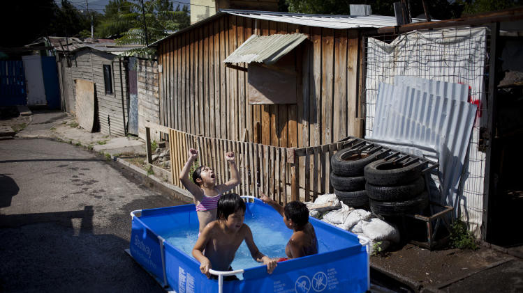 "Children play in at a pool in the street of the San Pablo shanty town in Santiago, Chile, Wednesday, Jan. 23, 2013.  European, Latin American and Caribbean leaders gathering for this weekend's economic summit will likely see only one side of Chile _ the polished, upscale country where tourists and investors stay in five-star hotels in a sparklingly clean financial district nicknamed ""Sanhattan,"" well away from Santiago's slums. (AP Photo/Victor R. Caivano)"