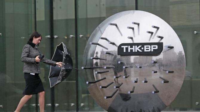A woman walks outside the TNK-BP headquarters in Moscow, Russia, Thursday, Oct. 18, 2012. Russia on Thursday downplayed concerns that Rosneft's possible purchase of BP's stake in the joint venture TNK-BP, which analysts say would reshape the country's oil industry and create the world's biggest oil and gas company, is likely to threaten competition. (AP Photo/Mikhail Metzel)