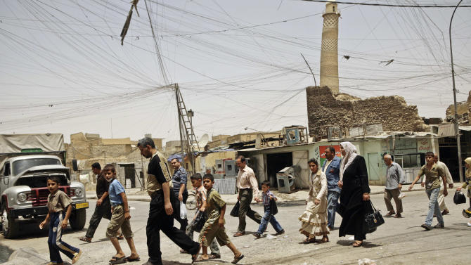 FILE - In this Monday, June 8, 2009 file photo, residents walk past the al-Hadba minaret in a busy market area in Mosul, Iraq. The fear, anger and sadness was palpable across Mosul on Saturday, July 26, 2014 as rumors made their way across Iraq's second-largest city. The militants who had taken over and purged it of some of its most cherished landmarks were eyeing their next target: al-Hadba minaret, an 842-year old tower that leans, like Italy's Tower of Pisa _ one of the country's most famous structures which decorates the 10,000 dinar bill until today.(AP Photo/Maya Alleruzzo, File)
