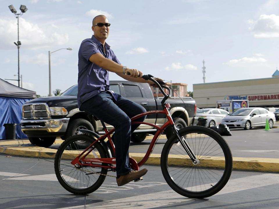 "In this July 24, 2013, photo, actor Coby Bell rides a bicycle between takes for an episode of ""Burn Notice"" in Miami. The cable spy drama is coming to an end after seven seasons with a big finale Thursday, Sept. 12, 2013. (AP Photo/Alan Diaz)"