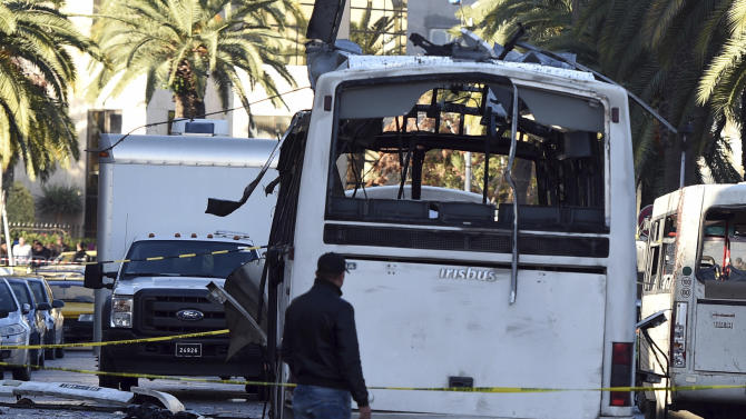 A plainclothes police officer walks beside the bus that exploded Tuesday in Tunis, Wednesday Nov.25, 2015. Tunisia's Interior Ministry says 10 kilograms (22 pounds) of military explosives were used in an attack on a bus carrying presidential guards that left at least 13 people dead. (AP Photo)