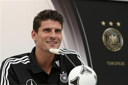 Germany's Gomez smiles during news conference ahead of Euro 2012 soccer match against Netherlands in Gdansk