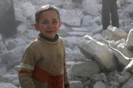 A boy cries as he stands amid rubble of collapsed buildings at a site hit by what activists said was a barrel bomb dropped by forces loyal to Syria's President Bashar al-Assad in Aleppo's al-Sakhour district March 6, 2014. REUTERS/Hosam Katan (SYRIA - Tags: POLITICS CONFLICT)