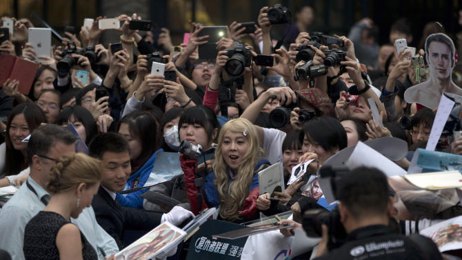 "In this Monday, March 24, 2014 photo, fans watch actress Scarlett Johansson, left in foreground, sign her autograph during a publicity event ahead of the April release of her movie ""Captain America: The Winter Soldier"" in Beijing. Captain America and Spiderman are seeking to dominate the Chinese box office in the coming weeks, proving that U.S. patriotic superheroes can overcome China's leeriness of foreign films if they promise big money. Chinese authorities, wary of outside cultural influences and competition, restrict the number of foreign movies shown in the mainland's cinemas to 34 each year. (AP Photo/Ng Han Guan)"