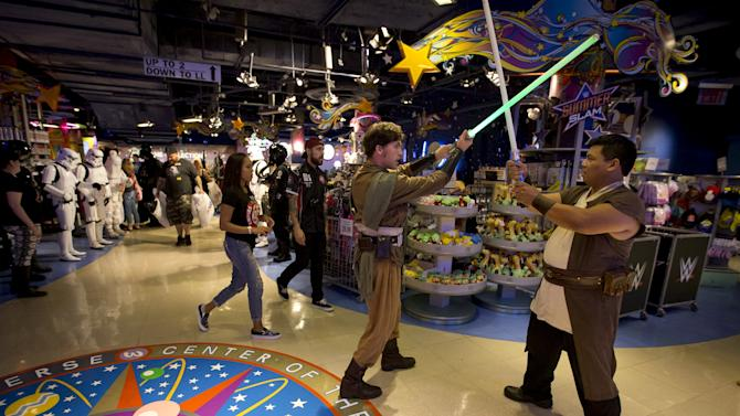 "People dressed as characters from ""Star Wars"" interact with their toy lightsabers as shoppers carry bags of purchases after toys of the film ""Star Wars: The Force Awakens"" went on sale at midnight at Toys R Us in Times Square in New York"
