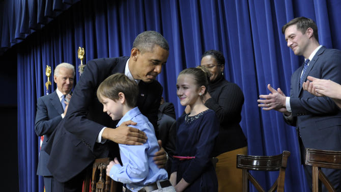 President Barack Obama, accompanied by Vice President Joe Biden, left, hugs eight-year-old letter writer Grant Fritz during a news conference on proposals to reduce gun violence, Wednesday, Jan. 16, 2013, in the South Court Auditorium at the White House in Washington. Obama and Biden were joined by law enforcement officials, lawmakers and children who wrote the president about gun violence following the shooting at an elementary school in Newtown, Conn., last month. (AP Photo/Susan Walsh)