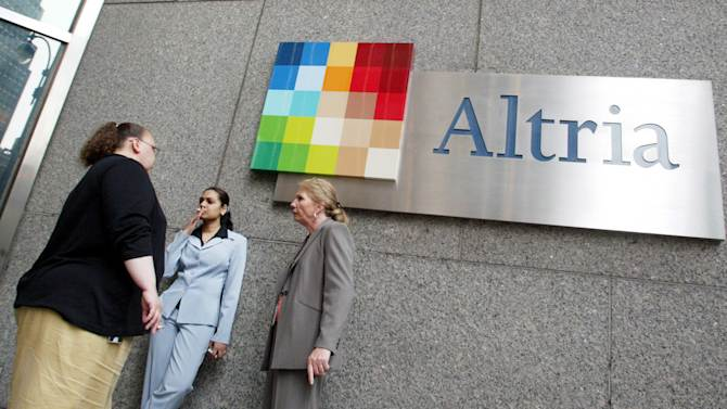 "FILE - In this May 12, 2004 file photo people smoke near the logo for Altria Group Inc., the parent of tobacco company Phillip Morris, at the companies offices in New York. An Illinois appellate court on Tuesday, April 2, 2014 reinstated a decade-old $10.1 billion verdict in a class-action lawsuit against Phillip Morris USA that found the nation's biggest cigarette maker misled customers about ""light"" and ""low tar"" designations. Philip Morris swiftly decried Tuesday's ruling by a three-judge panel of the Mount Vernon-based 5th District Appellate Court, saying it would ask the Illinois Supreme Court to review the matter. (AP Photo/Diane Bondareff, File)"