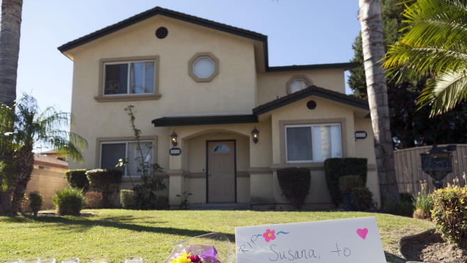Flowers and votive candles are seen outside the home of the owners of a family-owned business, United States Fire Protection Services, in Downey, Calif. Thursday, Oct. 25, 2012. A gunman killed three people and injured two, including a 13-year-old boy, Wednesday in two separate attacks on a family at its suburban Los Angeles business and nearby residence. Police say the five family members who were shot had been targeted by the gunman.  (AP Photo/Damian Dovarganes)