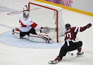 Latvia's Indrasis attempts a shot on Canada's goalie Price during the second period of their men's quarter-finals ice hockey game at the Sochi 2014 Winter Olympic Games