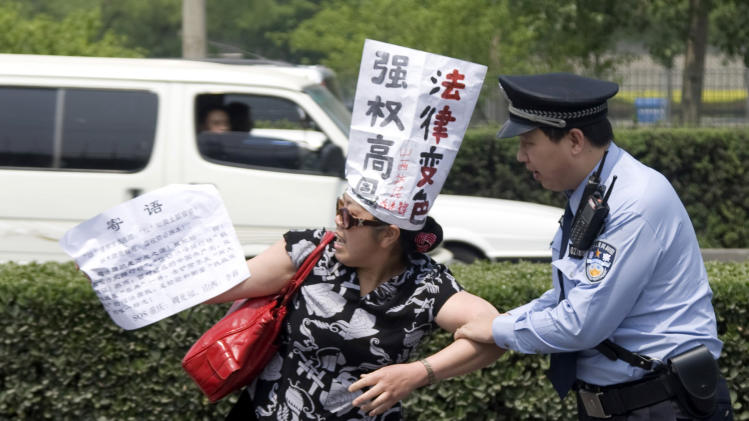 """FILE - In this May 4, 2009 file photo, a Chinese police officer tries to restrain a Chinese petitioner protesting against corruption and legal injustice on a road near a hotel in Beijing, China. Chinese authorities have shut down or frozen the microblog accounts of several prominent liberal intellectuals and harassed rights lawyers lobbying against unofficial """"black jails,"""" underlining the determination of the country's new leadership to control dissent even as it vows to root out corruption. (AP Photo/Ng Han Guan, File)"""