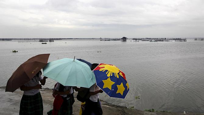 School girls with umbrellas take a stroll after classes were suspended due to bad weather, at a park in front of Laguna de Bay, in Paranaque