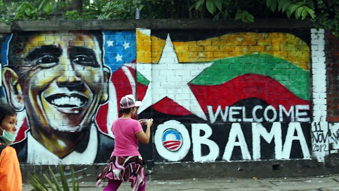 "A woman takes a photo of a wall painting created by Myanmar graffiti artists to welcome U.S. President Barack Obama on a street in Yangon, Myanmar, Saturday, Nov. 17, 2012. Obama will visit Myanmar on Monday, in a first for a sitting U.S. president. White House officials on Thursday said he will use his visit ""to lock down progress and to push on areas where progress is urgently needed"" — most notably freeing political prisoners and ending ethnic tensions in the western state of Rakhine and the northern state of Kachin. Obama's stop in Myanmar, scheduled to last about six hours, is the centerpiece of his first foreign tour since winning re-election. (AP Photo)"