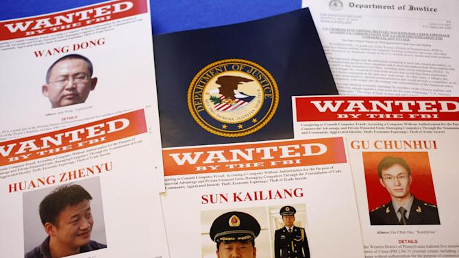 FILE - In this May 19, 2014, file photo, press materials are displayed on a table of the Justice Department in Washington, before Attorney General Eric Holder was to speak at a news conference to announce that a U.S. grand jury has charged five Chinese hackers with economic espionage and trade secret theft, the first-of-its-kind criminal charges against Chinese military officials in an international cyber-espionage case. The United States in July 2014 will urge China to resume discussions on cybersecurity that were suspended abruptly after the U.S. charged five Chinese military officers with hacking into U.S. companies to steal trade secrets, a U.S. official said June 26. (AP Photo/Charles Dharapak, File)