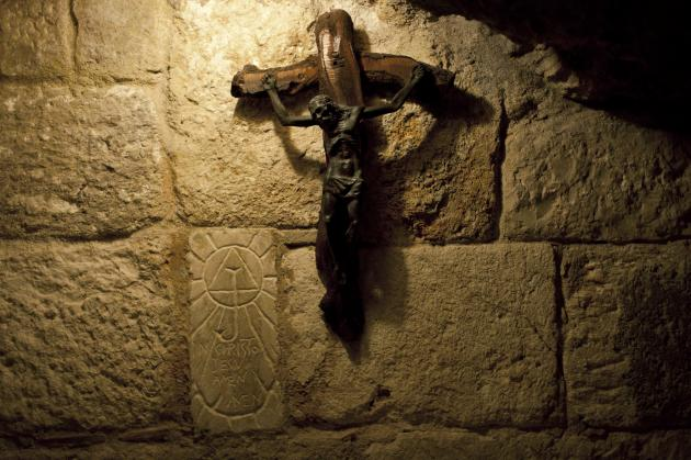 In this Tuesday Dec. 10, 2013 photograph, a crucifix is seen in the St. Jerome's Cave underneath the Church of the Nativity in the West Bank city of Bethlehem. To visitors arriving in Bethlehem fo