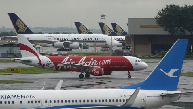 AirAsia's QZ8501 from Surabaya to Singapore, taking same code as missing plane which took off 24 hours earlier, taxis at Changi Airport in Singapore