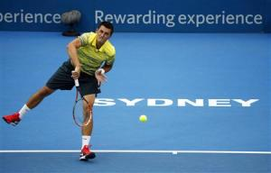 Bernard Tomic of Australia serves to Marcel Granollers of France during their first round match at the Sydney International tennis tournament
