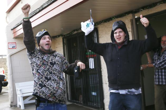 Damian Stasek and Sterling Hamilton celebrate buying recreational marijuana at the BotanaCare store in Northglenn