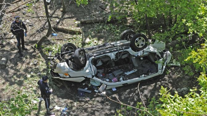 Police investigate the destroyed van that plunged over the Bronx River Parkway, Sunday April 29, 2012, in New York. Authorities say the out-of-control van plunged off a roadway near the Bronx Zoo, killing seven people, including three children. (AP Photo/ Louis Lanzano)