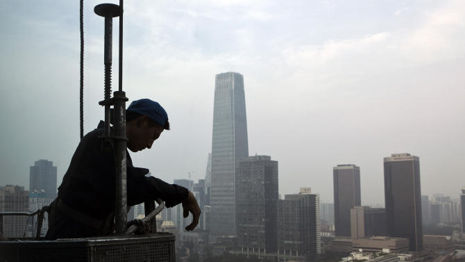 FILE - In this Aug. 1, 2011 file photo, a Chinese worker takes a rest on the suspended platform as he cleans glass windows of a building while high-rise buildings in the central business district are seen in the backdrop in Beijing, China. A skyscraper building boom in China and India may be a sign of an impending economic correction in two of Asia's largest economies, according to a new report by Barclays Capital. (AP Photo/Andy Wong, File)
