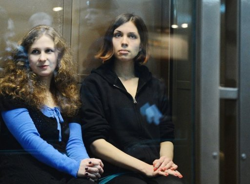 "The two jailed members of ""Pussy Riot"" Maria Alyokhina (left) and Nadezhda Tolokonnikova sit in a glass-walled cage during their appeals hearing at a Moscow courthouse in October 2012. A Russian court has issued an order to limit access to the videos of performances by the jailed feminist punk band -- ruling the films to be extremist."