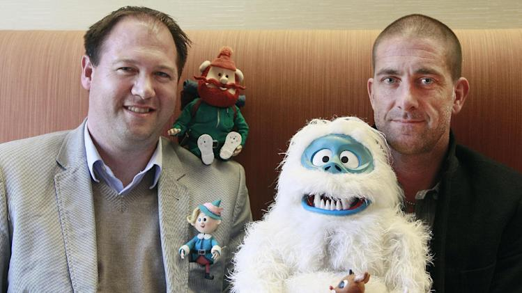 This Nov. 15, 2011 photo, shows Aaron Lilly, Microsoft Senior MarCom Architect, left, and Sean Carver, Bing Director of Advertising, pose with Yukon Cornelius, from top left, Hermey, The Abominable Snowman, and Rudolph the Red Nose Reindeer, all figures from the animated show Rudolph the Red Nose Reindeer, at the Microsoft office in San Francisco. (AP Photo/Jeff Chiu)