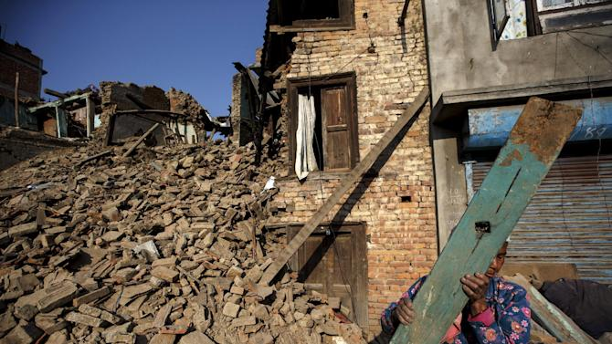 An earthquake survivor clears the debris of her collapsed house in Bungamati Village, on the outskirts of Kathmandu