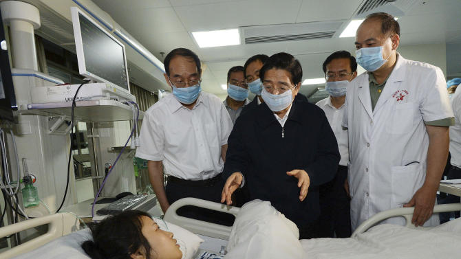In this photo taken Saturday, June 8, 2013, China's Public Security Minister Guo Shengkun, center, visits a woman injured in an express bus fire on June 7 that killed 47 as she recovers at a hospital in Xiamen in southeastern China's Fujian province. The official version of the last week's fire that gutted the bus in a prosperous port city in southeast China and left bodies piled up inside has been greeted with a derision by suspicious netizens that shows deep-seated distrust between Chinese and their government. (AP Photo) CHINA OUT