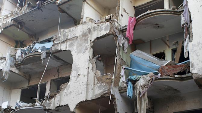 A Pakistani man stands in a damaged apartment which was destroyed along with other buildings in a Sunday evening car bombing that killed scores of people, in Karachi, Pakistan, Monday, March 4, 2013. Members of Pakistan's Shiite community were digging Monday through the rubble of a massive car bombing that targeted members of the minority sect leaving a mosque. (AP Photo/Shakil Adil)