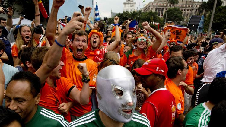 Fans of the Netherlands national soccer team celebrate the second goal of their team against Mexico as they watch the World Cup round of 16 match on a live telecast inside the FIFA Fan Fest area during the 2014 soccer World Cup in Sao Paulo, Brazil, Sunday, June 29, 2014. The Netherlands staged a dramatic late comeback, scoring two goals in the dying minutes to beat Mexico 2-1 and advance to the World Cup quarterfinals. (AP Photo/Rodrigo Abd)
