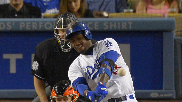 Los Angeles Dodgers' Hanley Ramirez, right, hits a two-run home run as San Francisco Giants catcher Buster Posey, lower left, and home plate umpire D.J. Rayburn look during the sixth inning of their baseball game, Tuesday, June 25, 2013, in Los Angeles. (AP Photo/Mark J. Terrill)