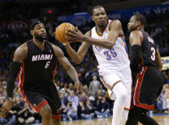 Oklahoma City Thunder forward Kevin Durant (35) drives between Miami Heat forward LeBron James (6) and guard Dwyane Wade (3) during the fourth quarter of an NBA basketball game in Oklahoma City, Thursday, Feb. 20, 2014. Miami won 103-81. (AP Photo/Sue Ogrocki)
