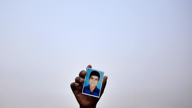 A man holds up a photograph of his missing relative as they plead for help at the site where the garment factory building collapsed Wednesday in Savar, near Dhaka, Bangladesh, Sunday April 28, 2013. At least 377 people are confirmed to have died in the Wednesday collapse of a shoddily-constructed building this week. The death toll is expected to rise but it is already the deadliest tragedy to hit Bangladesh's garment industry, which is worth $20 billion annually and is the mainstay of the economy.(AP Photo/Wong Maye-E)