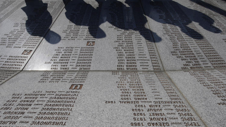 War veterans from the Balkan war of the 1990's  pay their respects in front of a marble stone with the names of victims at  the memorial center Potocari, near Srebrenica, 150 kms northeast of Sarajevo, Bosnia on Saturday, Nov.17, 2012. Veterans from opposite sides of the brutal Balkan wars paid their respects to the victims of the worst massacre in Europe since World War II. The small group of former fighters from Bosnia, Serbia and Croatia laid flowers Saturday at the memorial dedicated to over 8,000 Muslim Bosnian men and boys who were executed in 1995 by Serb forces in the eastern Bosnian town of Srebrenica.(AP Photo/Amel Emric)