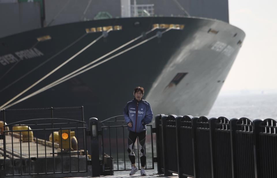 A man runs outside a container terminal in Tokyo, Wednesday, Jan. 25, 2012. Japan reported its first annual trade deficit since 1980 as it imported expensive energy to offset shortfalls caused by the devastating tsunami and manufacturers shifted production overseas to avoid the damage inflicted by the strong yen. (AP Photo/Junji Kurokawa)