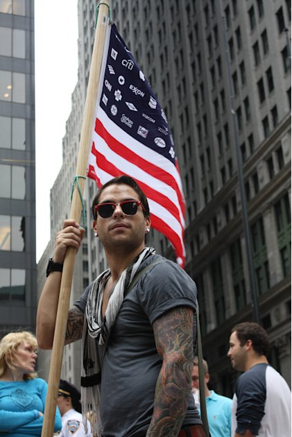 A protester bearing a flag where the stars of the American flag have been replaced with corporate logos.