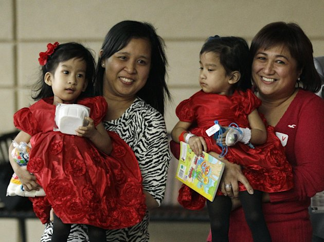 Angelina Sabuco, at left, is held by her mother Ginady Sabuco and twin sister Angelica, is held by aunt Marita Sabuco, at Lucile Packard Children&#39;s Hospital, Monday, Nov. 14, 2011 in Stanford, Calif. The twin sisters, who were born joined in the chest an abdomen, are preparing to go home after an intricate surgery by a group of Lucile Packard doctors to separate them. (AP Photo/Marcio Jose Sanchez)