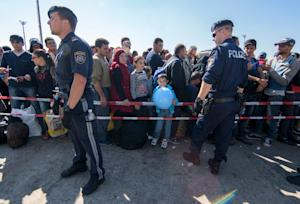 Police stand in front of migrants waiting to board…
