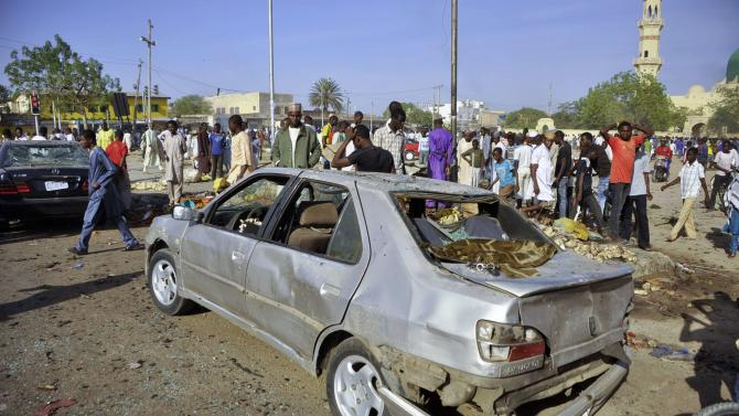 A car is seen damaged at a scene of multiple bombings at Kano Central Mosque